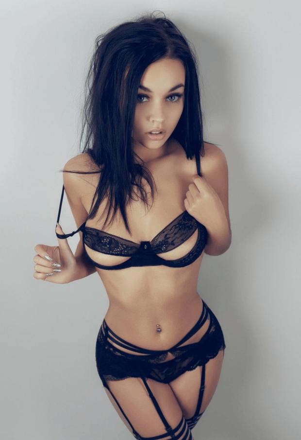 Брюнетка в сексуальном белье в чулках и поясе с подвязками