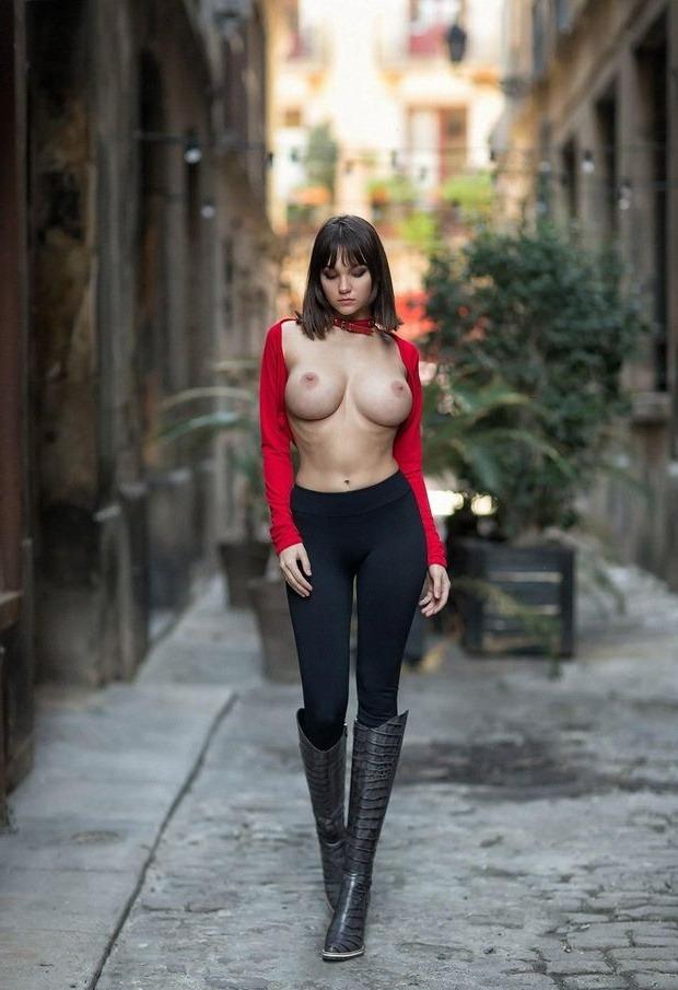 Красивая девушка с большими сиськами в сапогах идёт по улице