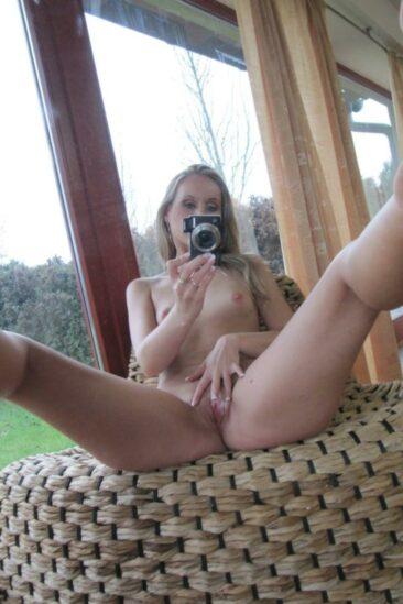 Женщина без трусиков и лифчика делает селфи перед зеркалом